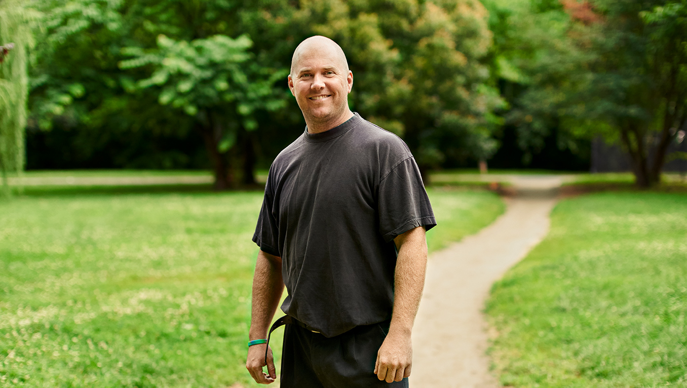 A young caucasian man standing in a path outdoors points into the camera while smiling
