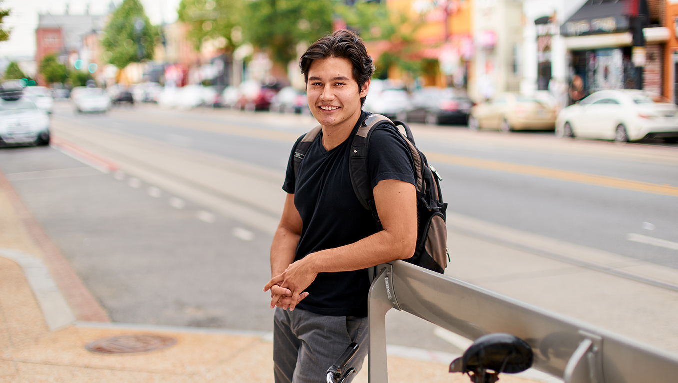 A young hispanic male smiling into the camera lifts both his hands up and gives the thumbs up gesture to the camera. He is standing on a busy intersection
