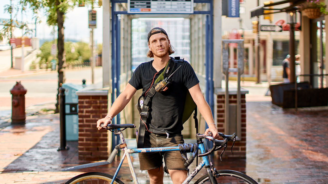 A young man with blonde hair and a hat straddles his bike and looks into the camera
